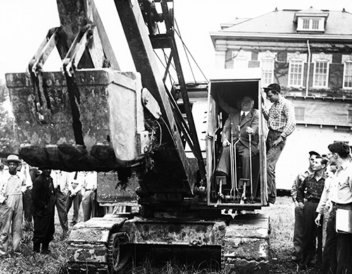 Dean John Lampe operating a steam shovel at the groundbreaking ceremony for Riddick Engineering Laboratories.