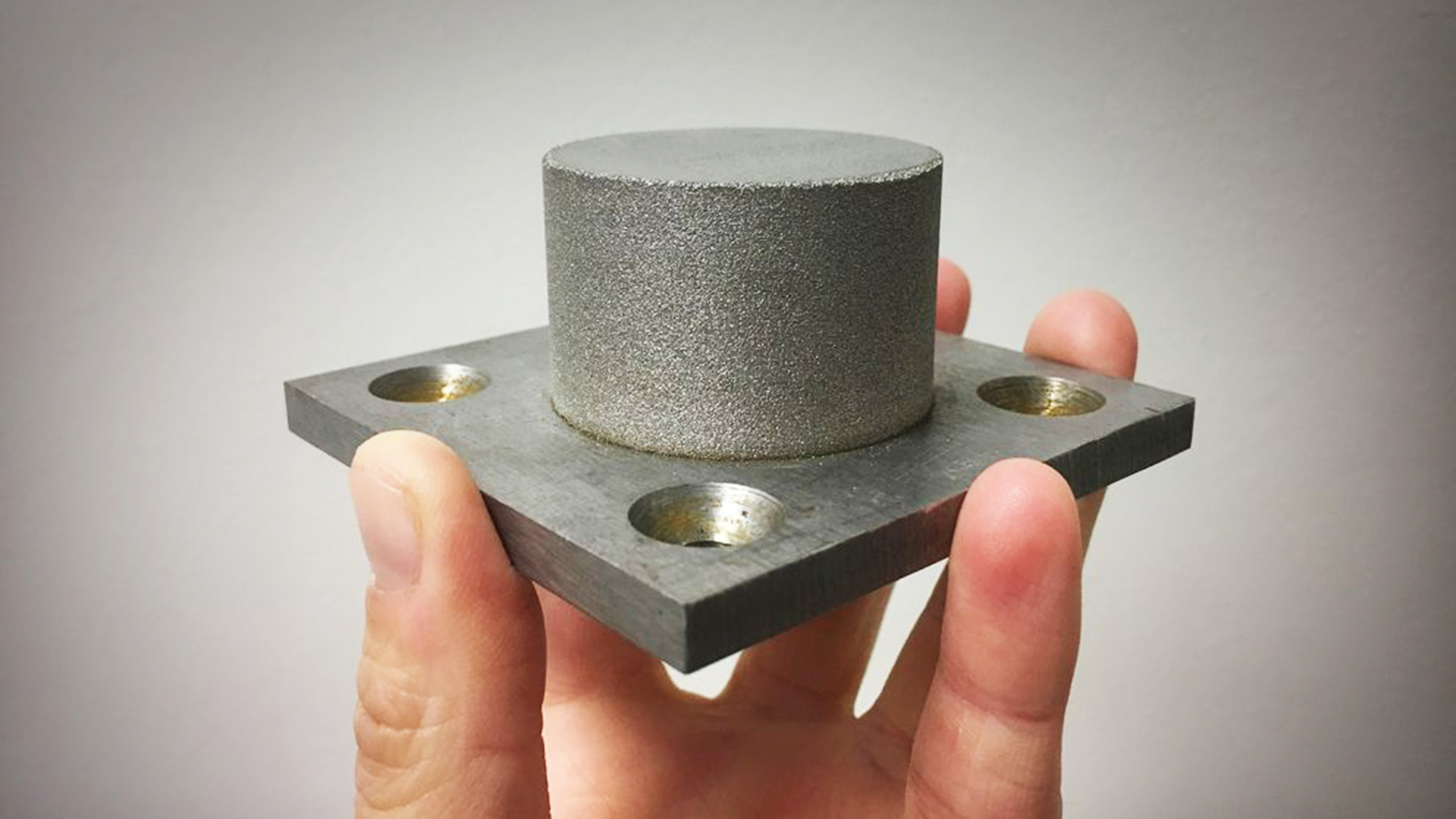 The cylinder is an amorphous iron alloy, or metallic glass, made using an additive manufacturing technique