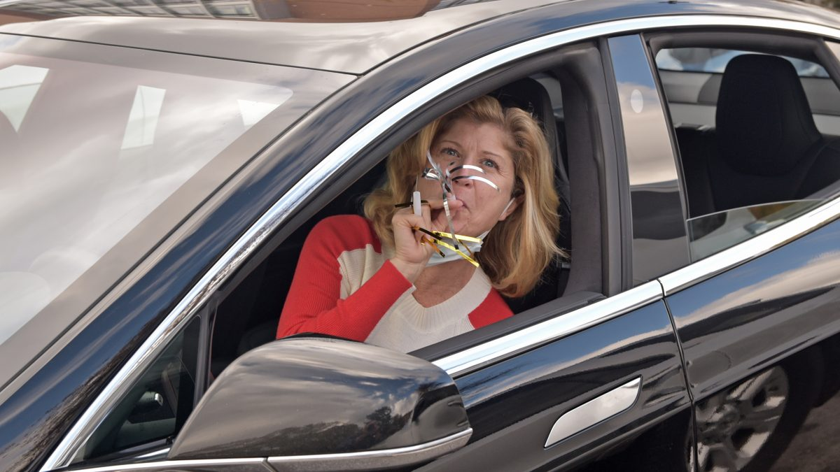 A mother blowing celebratory noise-makers in her car.