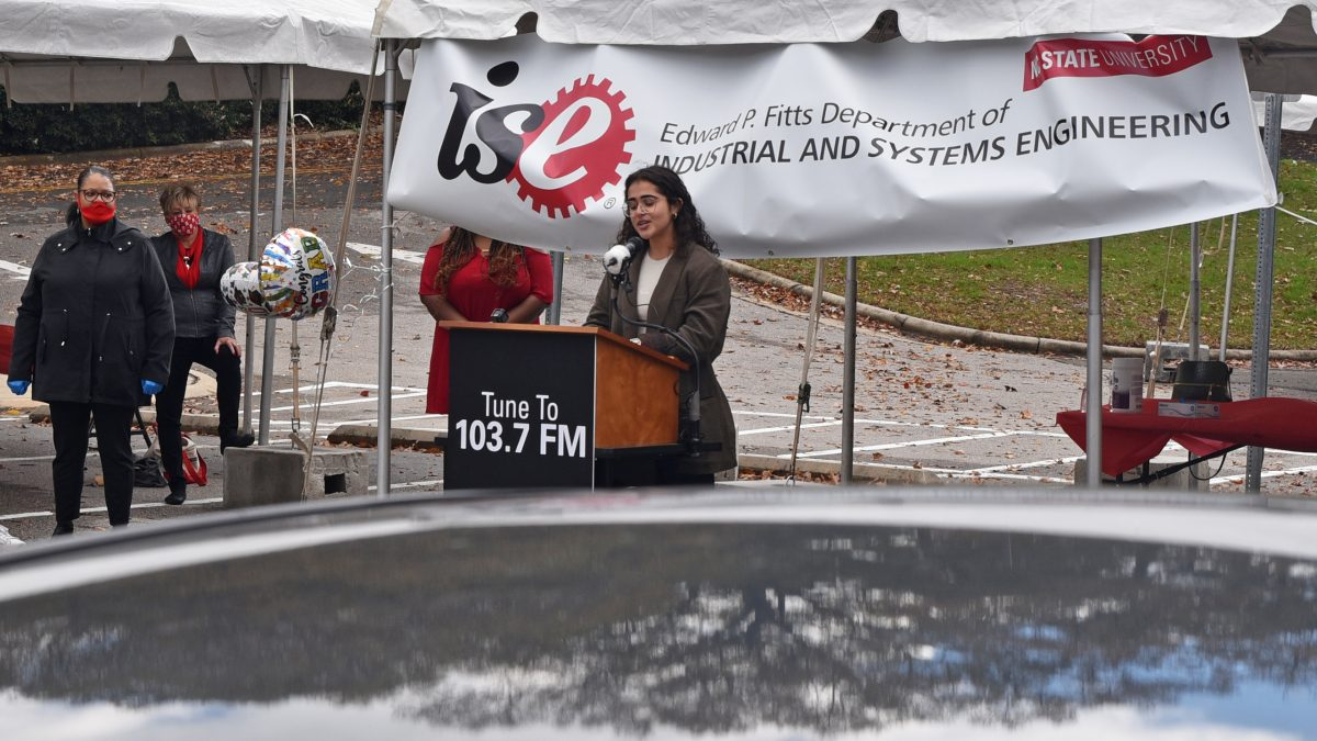 A female student gives remarks at the podium.