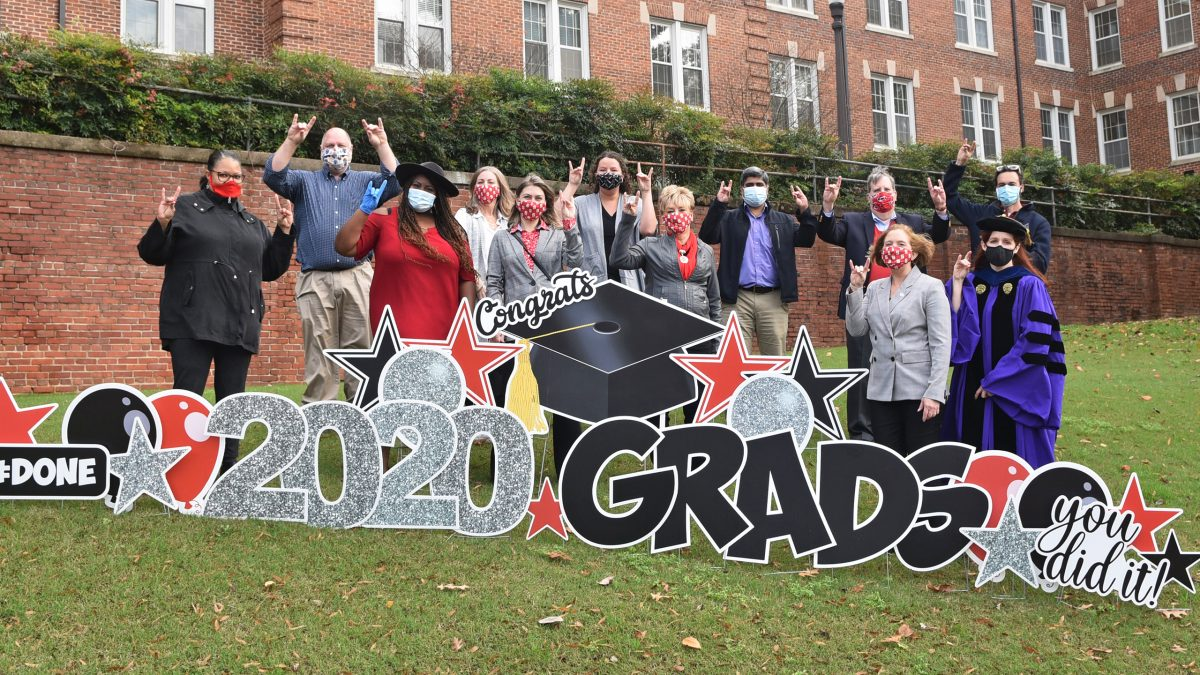 ISE staff standing behind the Graduation sign.