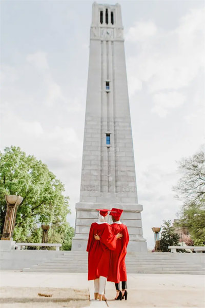 Iman and Salam Ibrahim look up at the Memorial Belltower in their graduation robes