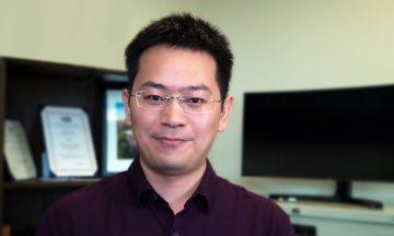 Xiaolei Fang standing in his office