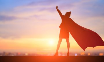 A business woman wearing a cape is pointing her fist in the air with the setting sun in the background